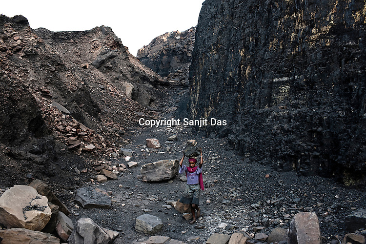 A young is seen carrying huge piles raw coal from the open cast mines in Borapahari in Jharia, Jharkhand, India.  Photo: Sanjit Das