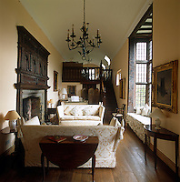 The galleried living room of this English manor house is furnished with a pair of damask-covered sofas and a cushioned window seat