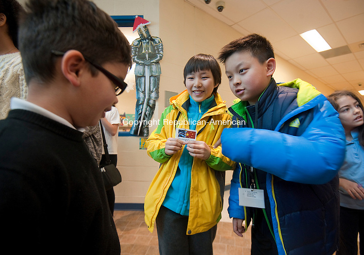 WATERBURY,  CT-021015JS03- Host family member Nicholas Andrade, 8, a third grade student at Carrington Elementary School in Waterbury in introduced to Zhuangshunhe Li, 10, left, and Jiabang Tang, 10, right, as they arrive at the school on Tuesday. 43 Chinese students are staying with local host families during a 3-day exchange. <br /> Jim Shannon Republican-American