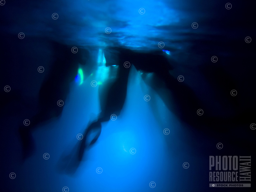 The underwater silhouette of snorkelers against light meant to illuminate manta rays feeding during a night trip, Big Island.
