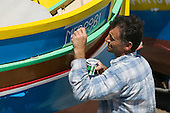Maltese Man painting a Luzzu, a Maltese fishing boat, in Marsaxlokk, Malta