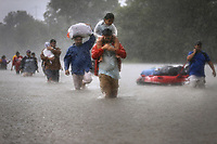 Residents carrying young children and belongings escape rising flood waters from Hurricane Harvey in Houston, Texas, U.S.A. on August 28, 2017.