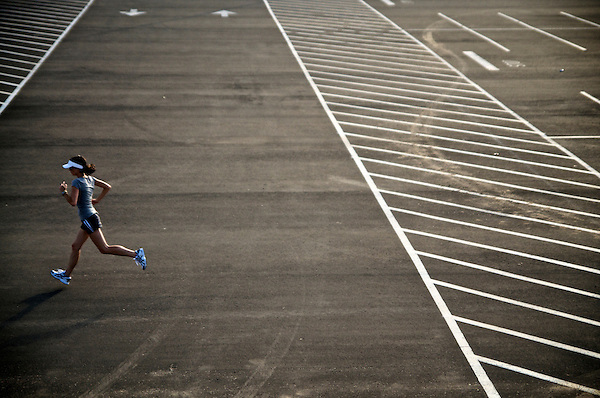 Female runner jogging across an empty parking lot.
