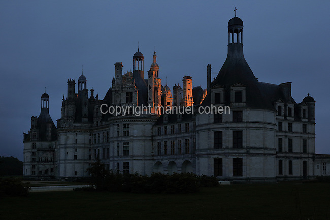 Chateau de Chambord in the evening, designed by Domenico da Cortona and built 1519-47 in French Renaissance style under King Francois I, at Chambord, Loir-et-Cher, France. The largest of the Loire Valley chateaux, Chambord has a central keep with 4 bastion towers on the corners, a moat and an elaborate decorative roofline. The chateau was listed as a UNESCO World Heritage Site in 1981. Picture by Manuel Cohen