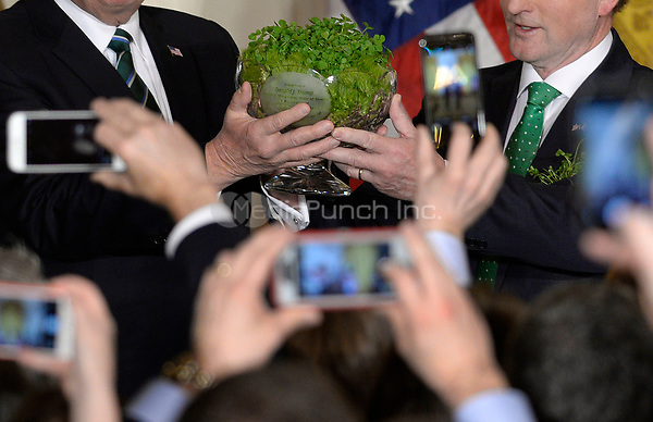 United States President Donald J. Trump, left, accepts a bowl of shamrocks from Prime Minister (Taoiseach) Enda Kenny of Ireland during a reception in the East Room of the White House in Washington, DC on March 16, 2017. <br /> Credit: Olivier Douliery / Pool via CNP /MediaPunch