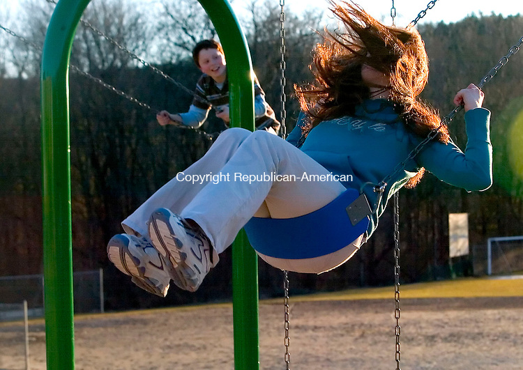 THOMASTON, CT- 29 MARCH 07- 032907JT09- <br /> Dan Nolte, 12, of Woodbury, watches his sister Katie, 15, as her red hair covers her face as it's lit by the sunset on the swings at the Black Rock School playground in Thomaston on Thursday.<br /> Josalee Thrift Republican-American
