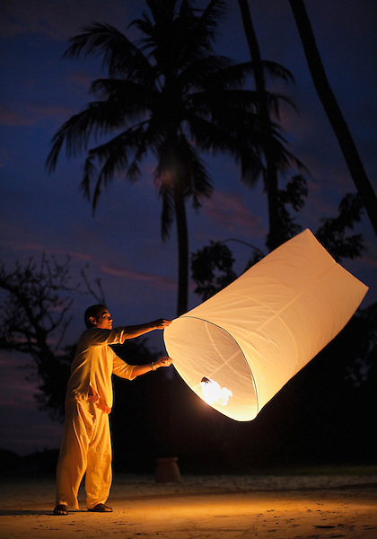 Man Holding Paper Khom Loy  Lantern at Kamalaya, Koh Samui, Thailand. A man holds a lit paper lantern on Ao Thai beach at Kamalaya resort.