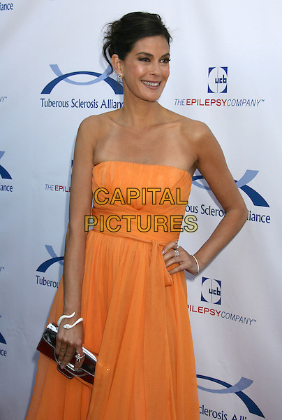 TERI HATCHER.7th Annual Comedy For A Cure benefiting The Tuberous Sclerosis Alliance held at the Avalon, Hollywood, California, USA..April 6th, 2008.half length yellow orange strapless dress hand on hip silver clutch bag purse tan lines .CAP/ADM/RE.©Russ Elliot/AdMedia/Capital Pictures.