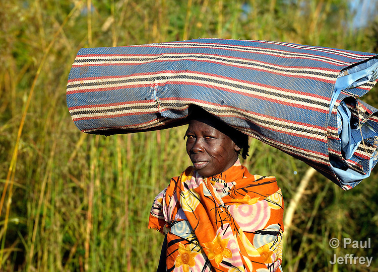 A woman walks with a mat on her head, near Bussera, South Sudan.