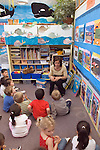 Berkeley CA  Preschool teacher engaging students in conversation in well-decorated aquatic-themed classroom.