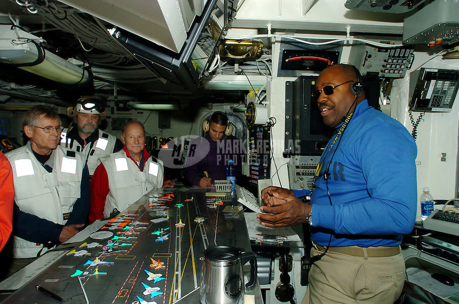 040608-N-6213R-027 Gulf of Alaska (Jun. 8, 2004) - The flight deck handler, Lcdr. Byron Rice (right) of Mandeville, Jamacia, speaks with Distinguished Visitors (DV's) in the flight deck control office aboard USS John C. Stennis (CVN 74). The handler is responsible for the safe movement and placement of aircraft aboard Stennis. Stennis and embarked Carrier Air Wing Fourteen (CVW-14) are currently at sea participating in Exercise Northern Edge, part of a scheduled deployment.  Photo by Mark J. Rebilas