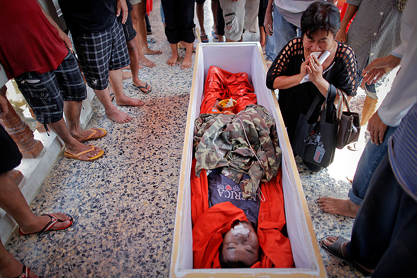 Sawani Zaelai, the mother of Thawatcha Busabim grieves over his coffin during a funeral procession at the Wat Preak Prachkor temple in Pathum Thani province, suburb of Bangkok October 19, 2011. 30-year old Thawatcha Busabim was electrocuted when he tried to use electric appliance at his flooded home in Pathum Thani. Flooding in the north, northeast and centre of the country has killed at least 317 people since July and damaged large areas of farmland in the country's worst floods in half a century.  REUTERS/Damir Sagolj (THAILAND)