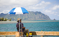 Local man under an umbrella fishing off the Heeiakea Harbor dock, with Koolau Mountains in the background