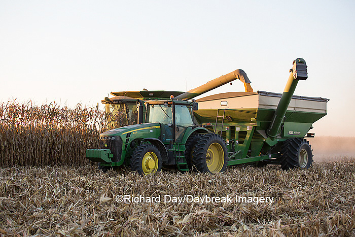 63801-06614 John Deere combine harvesting corn while unloading corn into wagon, Marion Co., IL