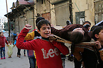 Syrian children carry the body of their friend as they play in a symbolic funeral in the northern Syrian city of Aleppo, on Jan. 22, 2016. Photo by Ameer al-Halbi