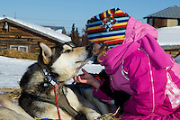 Young Ella Bird Mercer gets a kiss from a Paul Johnson dog as she pets it on Saturday morning at the Shageluk checkpoint during Iditarod 2011