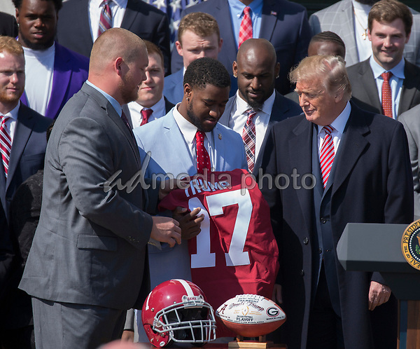 United States President Donald J. Trump receives a jersey from team members during the welcoming ceremony of the 2017 NCAA Football National Champions: The Alabama Crimson Tide to the White House in Washington, DC, March 10, 2018. Photo Credit: Chris Kleponis/CNP/AdMedia