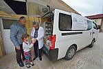 A displaced father and daughter get a prescription filled by Pharmacist Aodeshu Yanan during the visit of a mobile clinic to the village of Sharafiya, Iraq, which was flooded with displaced families when the Islamic State group took over nearby portions of the Nineveh Plains in 2014. The clinic is a program of the Christian Aid Program Nohadra - Iraq (CAPNI). Yanan was also displaced by ISIS.
