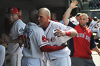 Third baseman Kevin Mager (32) of the Greenville Drive, right center, is congratulated by Jose Vinicio (36) and teammates after they gave him the silent treatment when he hit his first professional home run in a game against the Delmarva Shorebirds on Monday, April 29, 2013, at Fluor Field at the West End in Greenville, South Carolina. Delmarva won, 6-5 in game one of a doubleheader. (Tom Priddy/Four Seam Images)