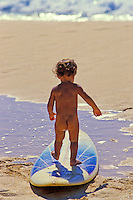 Little boy playing on a surfboard at the beach