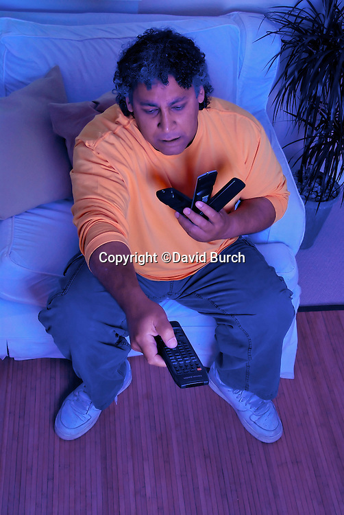 Man struggling with television remote controls
