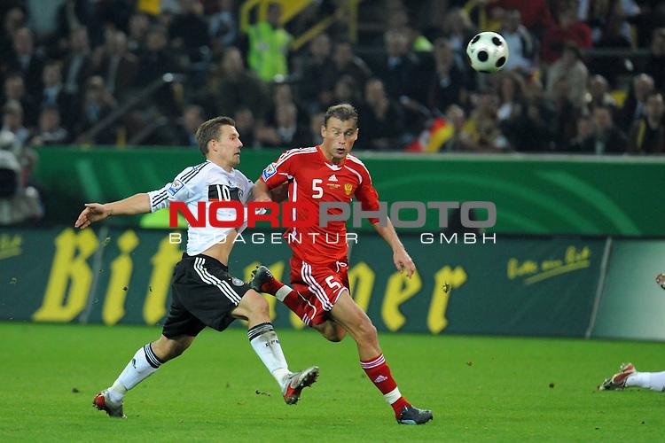 Fussball, L&auml;nderspiel, WM 2010 Qualifikation Gruppe 4 Westfalen Stadion Dortmund ( SIGNAL IDUNA PARK )<br />  Deutschland (GER) vs. Russland ( RUS )<br /> <br /> <br /> Lukas Podolski  (Ger /  Bayern Muenchen #10) wird von Vasili Berezutskiy (RUS #05)  gehalten<br /> <br /> Foto &copy; nph (  nordphoto  )<br />  *** Local Caption ***
