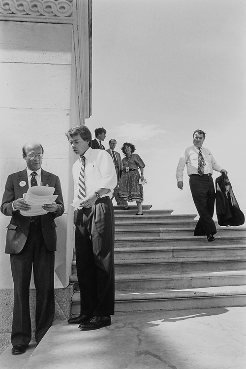 After the vote by the Rules Committee and leading up to the bill vote, Members are leaving the Capitol for their offices. Rep. Michael J. Kopetski, D-Ore. consults with staffer, Scott Barstow. Greg Laughlin heads down stairs. Gene Taylor at top with Annebau of ABC on May 27, 1993. (Photo by Maureen Keating/CQ Roll Call)