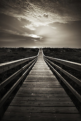 A boardwalk leads to the beach under an ominous sky in St. Augustine.