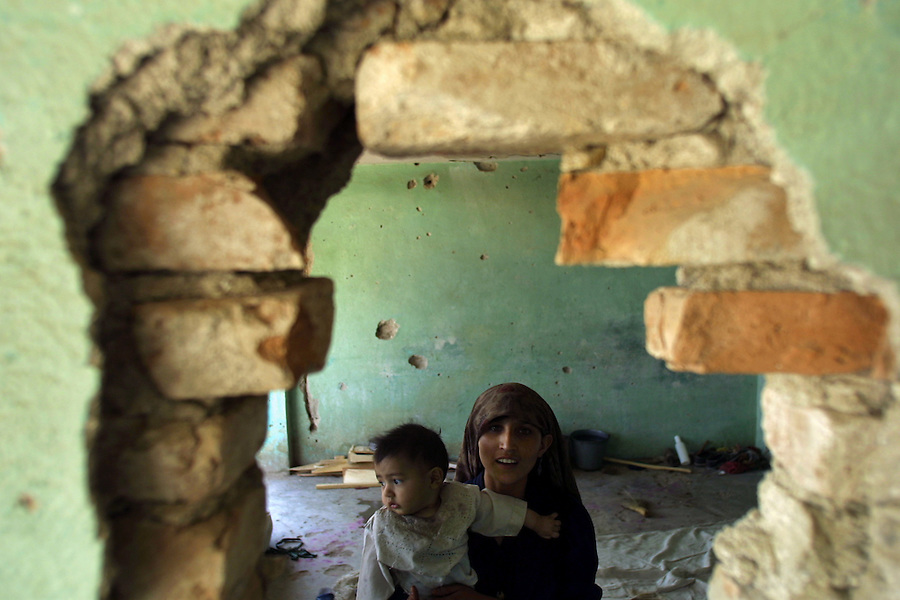 A mother and her baby, squatting in an abandoned, bombed out building in Kabul.