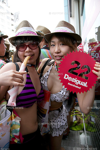 """Tokyo, Japan - Customers in swimsuit pose for cameras outside the Desigual store in Tokyo's Harajuku fashion district. A fashion chain called """"Seminaked Party by Desigual"""" offers the first 100 customers (wearing swimsuit) free clothing items at the grand opening in Tokyo, Japan, June 22, 2013. More than 4,000 people attend the Seminaked Party around the world. (Photo by Rodrigo Reyes Marin/AFLO)"""