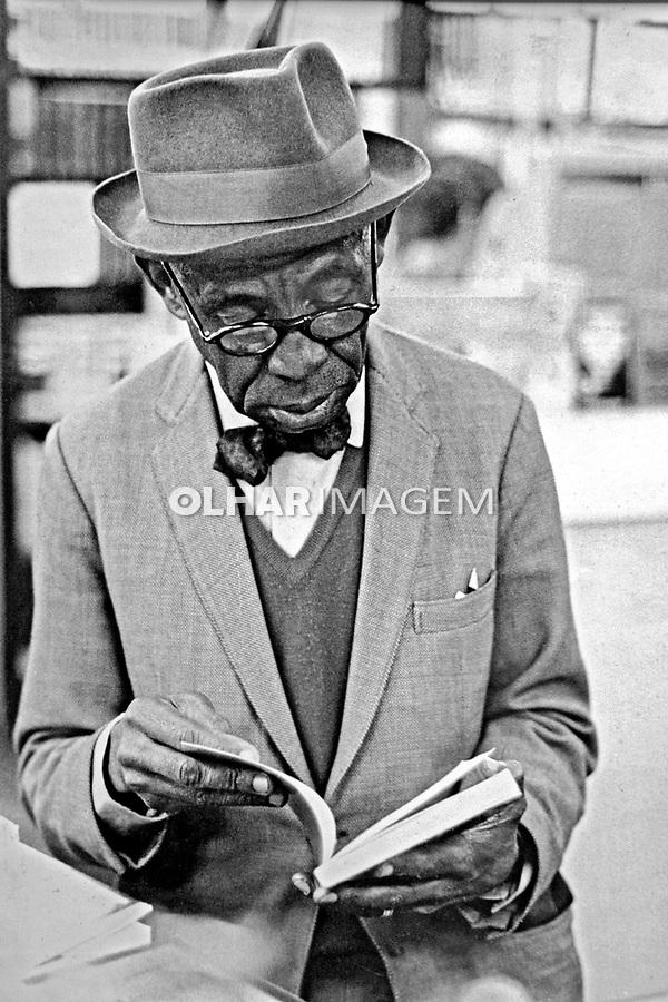 Homem lendo livro em livraria no centro de Sao Paulo. 1970. Foto de Juca Martins.