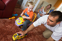 A father and mother playi with their two small children, a baby and a toddler, at home on their living room carpet.  The older boy is riding a sit-on car and his father is pushing a toy bus. They are having a race...09/07/2011.Hampshire, England, UK