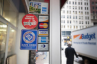 A sticker promoting Yelp, the online crowdsourcing review site, is seen on Friday, March 2, 2012 on the door of a pizza restaurant in New York on the day of Yelp's initial public offering. The eight year old, still unprofitable company priced its IPO at $15 per share. Beside restaurants, Yelp carries reviews by viewers of a multitude of businesses and services. (© Richard B. Levine)