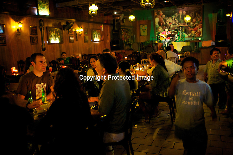 """Guests enjoy their dinner while a performer sings on the stage of the Hobbit House in Makate, Manila in Philippines. The restaurant/bar is entirely staffed by """"little people.""""  Photo: Sanjit Das"""