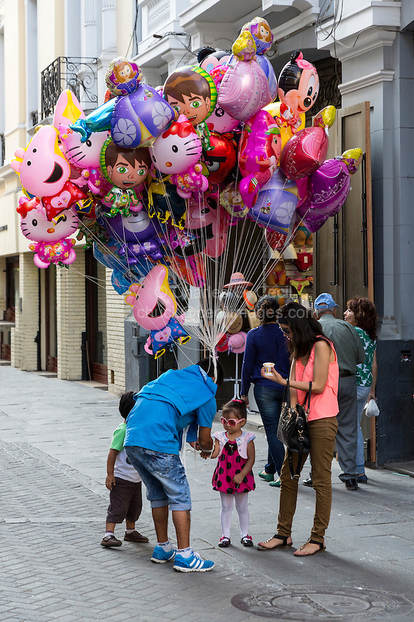 Lima, Peru.  Mother Buying a Balloon for her Child.