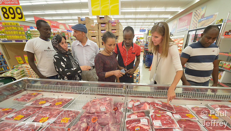 Penny Gushiken (second from right) leads a cultural orientation class for newly arrived refugees in Lancaster, Pennsylvania. During a visit to a supermarket, participants discuss available food items, including different types of meat. The class is sponsored by Church World Service. <br /> <br /> Photo by Paul Jeffrey for Church World Service.