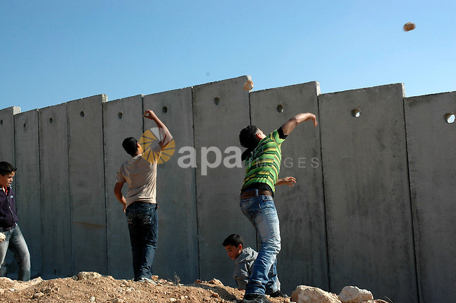 Palestinians throw stones at Israeli forces during a demonstration against Israel's separation barrier in the West Bank village Nillin near Ramallah on Nov 20, 2009. Photo by Nedal Shtieh
