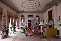 The drawing room is decorated with elaborate plasterwork moulding and vibrantly upholstered furniture