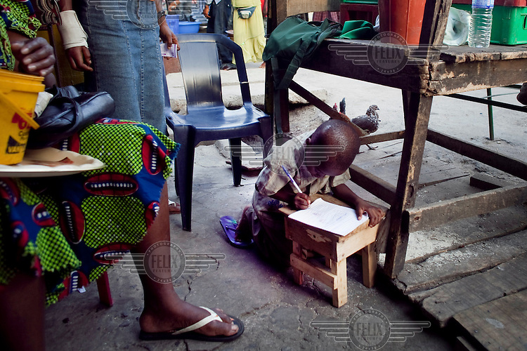 A child studies on the floor of his mother's shop on Lagos Island, an area in the centre of the city that has been largely abandoned by the city's elite as it is seen to be overrun by crime and area boy gangs.