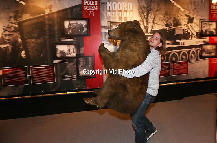 Foto: VidiPhoto<br /> <br /> GROESBEEK - Leerlingen van basisschool Op de Horst ontvangen dinsdag de dronken beer Wojtek (vrolijke strijder) met een Poolse 'biertje' uit de Tweede Wereldoorlog. De beer was de mascotte van Poolse soldaten die vanaf 1942 via Noord-Afrika hielpen Europa te bevrijden. Een replica van het dier speelt een grote rol in de tentoonstelling &quot;De Polen. Bevrijders in Ballingschap&quot; van het Nationaal Bevrijdingsmuseum in Groesbeek. Wojtek werd als welp geadopteerd en kreeg zelfs een rang (korporaal) in het leger om hem in 1944 vanuit Afrika naar Napels te kunnen verschepen en zo Europa te helpen bevrijden. De beer moest de voedselvoorraden bewaken en werd door zijn heldhaftige gedrag bevorder en later ook weer gedegradeerd omdat hij in dronken toestand een aantal legertenten vernielde. Na de oorlog bleef Wojtek net als vele Poolse soldaten in Schotland. Hij werd opgenomen in de dierentuin van Edinburgh. Met enige regelmaat was er verbazing en onrust in de dierentuin als er weer eens Poolse veteranen in het berenverblijf waren geklommen om even met Wojtek te stoeien. Wojtek is tot 31 mei te zien in het Nationaal Bevrijdingsmuseum.
