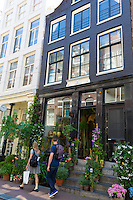 Shoppers pass traditional florist shop in the Nine Streets - De Negen Straatjes - 9 Streets district of Jordaan, Amsterdam