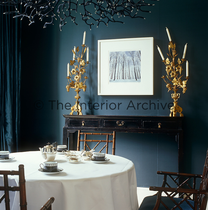 Ornate gilded candlesticks on a console table in the dining room of the Grove Hotel, Hertfordshire strike a dramatic note against the midnight blue walls