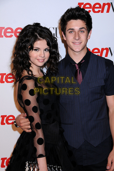 SELENA GOMEZ & DAVID HENRIE .Teen Vogue's 2008 Young Hollywood Issue Party at the Los Angeles County Museum of Art, Los Angeles, California, USA..September 18th, 2008.half length black dress sheer polka dot sleeves blue waistcoat shirt .CAP/ADM/BP.©Byron Purvis/AdMedia/Capital Pictures.
