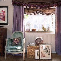 An armchair upholstered in turquoise velvet has been juxtaposed with violet swagged curtains in a stunning colour contrast