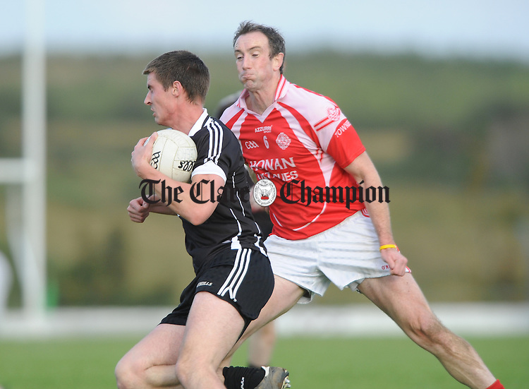 Colm Dillon of Doonbeg in action against David Russell of Eire Og during their senior championship game at Kilmihil. Photograph by John Kelly.