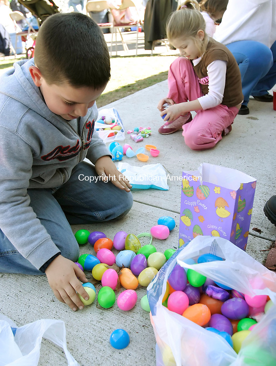 NAUGATUCK, CT, 09 April 2006- 040906BZ03- Justin Fernendes (CQ), 7, and Briana Ercoli, 7, of Waterbury, check their Easter Eggs for candy and prizes after the annual Easter Egg Hunt at Julie Sampaio's Naugatuck home Sunday afternoon.  Sampaio said there were 2,700 eggs scattered for the kids to find.<br />  Jamison C. Bazinet Republican-American
