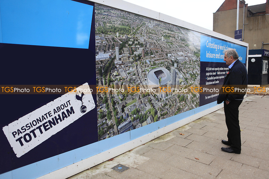 A fan looks at a picture of an artists impression showing Tottenham's new stadium development during Tottenham Hotspur FC Ground Redevelopment at White Hart Lane, London, England on 10/11/2015