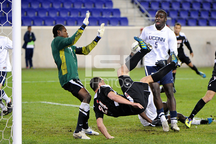 Connecticut Huskies goalkeeper Andre Blake (18) blocks the shot of Austin Berry (24) of the Louisville Cardinals. Connecticut defeated Louisville 1-0 during the first semifinal match of the Big East Men's Soccer Championships at Red Bull Arena in Harrison, NJ, on November 11, 2011.