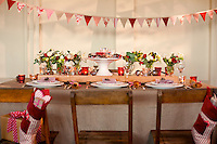 A rustic dining table has been decorated for Christmas with flowers, bunting and twinkling tea lights