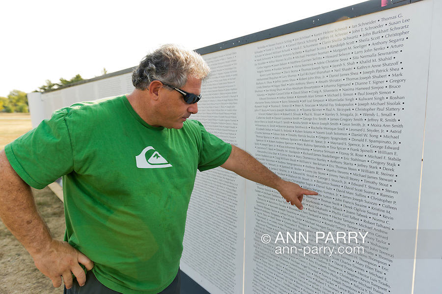 """East Meadow, New York, U.S. 11th September 2013. MIKE BERNSTEIN, of East Meadow, points to the name of his friend, NYC firefighter Daniel Suhr, who, Bernstein explained, died when someone who jumped from window of Twin Tower landed on him as Suhr was rushing into the tower. The Global War on Terror """"Wall of Remembrance"""" a traveling memorial on display in New York for the first time, is at Eisenhower Park on the 12th Anniversary of the terrorist attacks of 9/11. The unique 94 feet long by 6 feet high wall has, on one side, almost 11,000 names of those lost on September 11, 2001, along with heroes and veterans who lost their lives defending freedom of Americans over past 30 years. On the wall's other side is a timeline, with photos, covering 1983 to present day."""